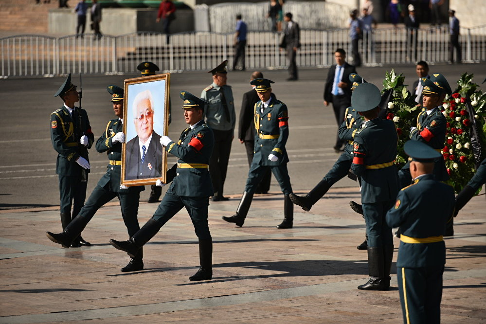 Улуттук Гвардия офицерлери Ала-Тоо аянтында мамлекеттик жана саясий ишмер Турдакун Усубалиевдин сүрөтүн көтөрүп бара жатышат.