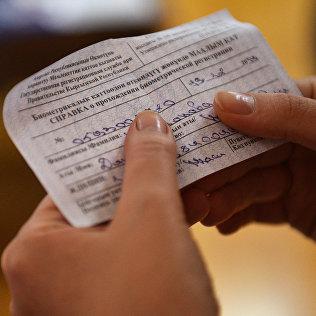 Человек держит справку о прохождении биометрической регистрации. Архивное фото
