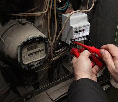 Электрик проверяет электросчетчики в подъезде жилого дома. Архивное фото