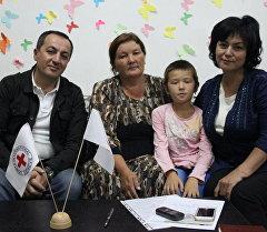 Жительница Джалал-Абада Тамара Исраилова с семьей и координатором программы Восстановление семейных связей Салтанат Абдыжапаровой.