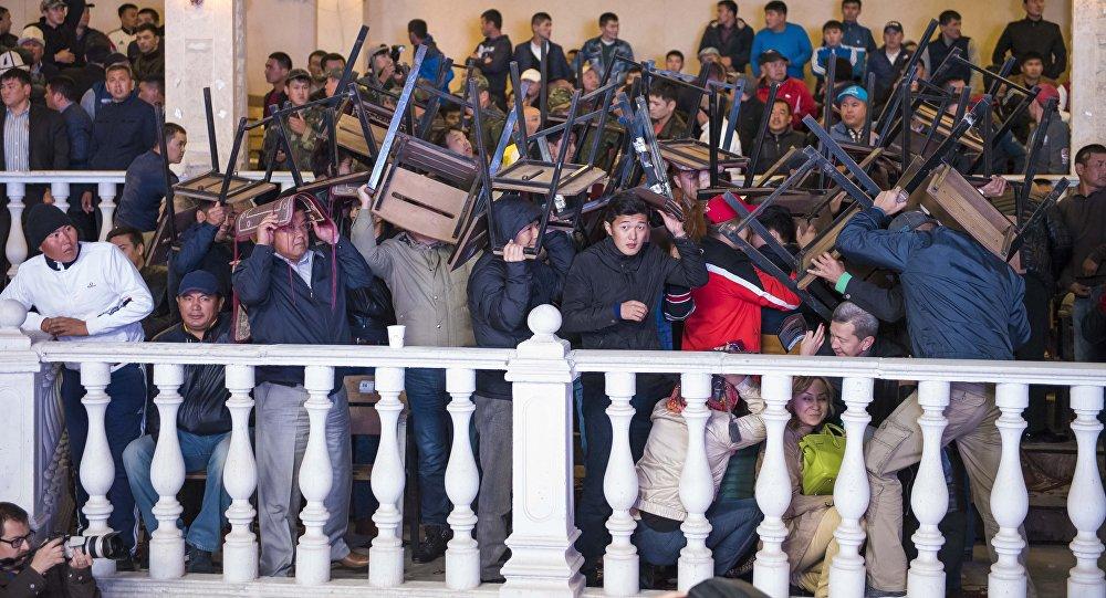 Ала-Тоо эс алуу борборунда өтүп жаткан беттешүүдө отургучтар менен сактанып аткан адамдар.