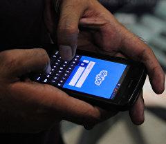 Мужчина с телефона открывает программу Skype. Архивное фото