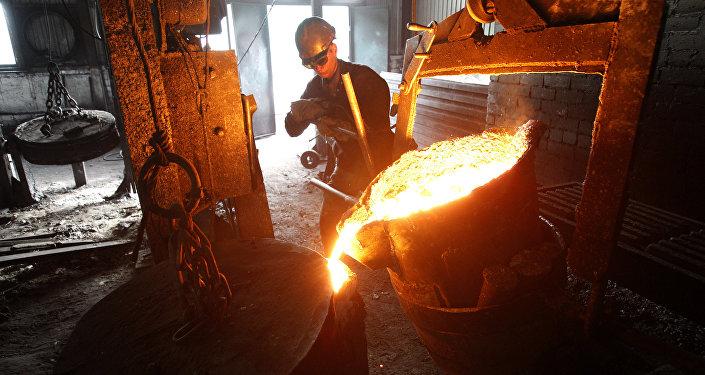 Работник заливает расплавленный чугун в формы. Архивное фото