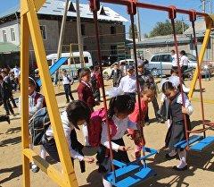 Дети играют на качелях в детском саду. Архивное фото