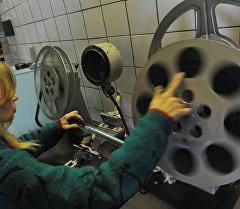 Кинотеатр кызматкери кинопроектти даярдоо кезинде. Архив