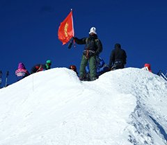 Учкун Жумакадыров на вулкане Эльбрус с флагом Кыргызстана.