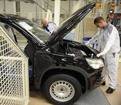 Volkswagen заводунун кызматкери автоуннаны текшерип жатат. Архив