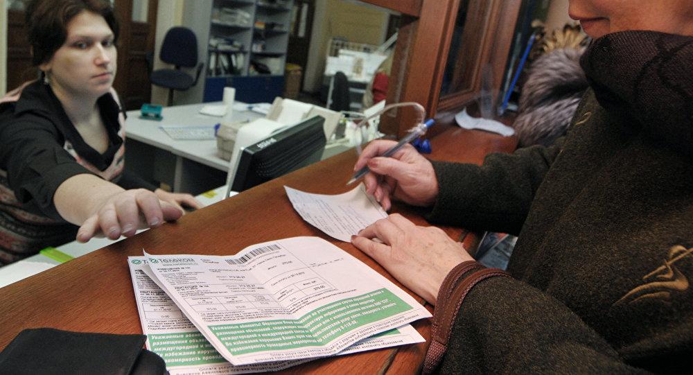 Женщина производит оплату жилищно-коммунальных услуг на почте. Архивное фото