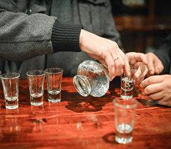 Алкоголдук ичимдик ичип жаткан адамдар. Архив