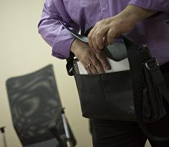Документтерди портфельге салып жаткан адам. Архив