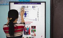 Девушка вытирает стенд с инструкцией пошаговых действий избирателя. Архивное фото