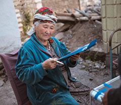 Жительница Бишкека во время досрочного голосования в Жогорку Кенеш.