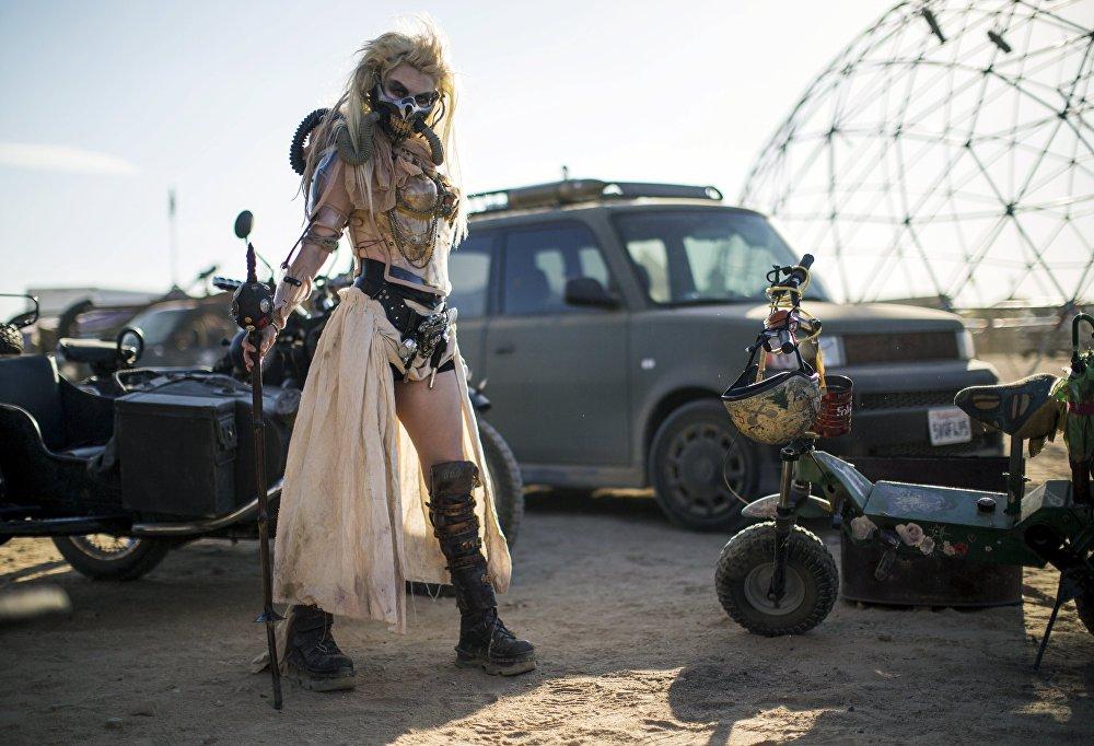 Акылсыз Макс каарманынын кийимин кийген Дезире Хепп (Desirae Hepp) Калифорниядагы Wasteland Weekend фестивалында. Иш-чарада Акылсыз Макстын стилинде жасалгаланган 100дөн ашык автоунаалар менен мотоциклдер болду.