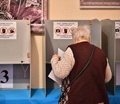 Избиратель во время голосования в одном из избирательных участков. Архивное фото