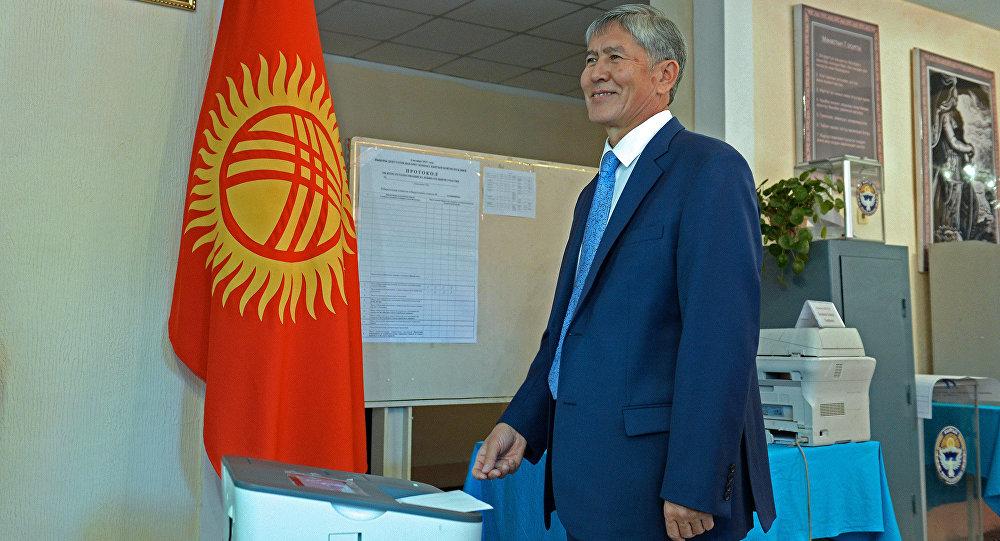 Президент Кыргызской Республики Алмазбек Атамбаев отпускает бюллетень в урну во время голосования. Архивное фото