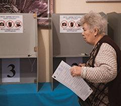 Избиратель на избирательном участке в городе Бишкек