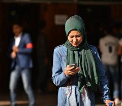 Девушка с телефоном возле избирательного участка в Бишкеке. Архивное фото