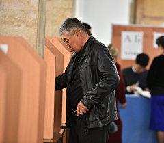 Мужчина голосует на одном из избирательных участков. Архивное фото