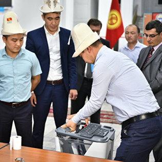 Члены комиссии снимают крышку урны для подсчета голосования. Архивное фото
