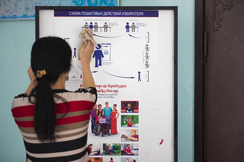 Девушка вытирает стенд с инструкцией пошаговых действий избирателя