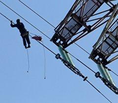 Промышленный альпинист на проводе линии электропередач. Архивное фото