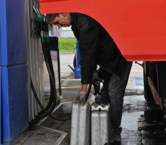 Водитель заливает топливо в канистры. Архивное фото