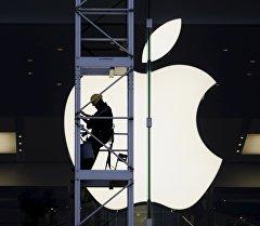 Рабочий на фоне логотипа компании Apple. Архивное фото