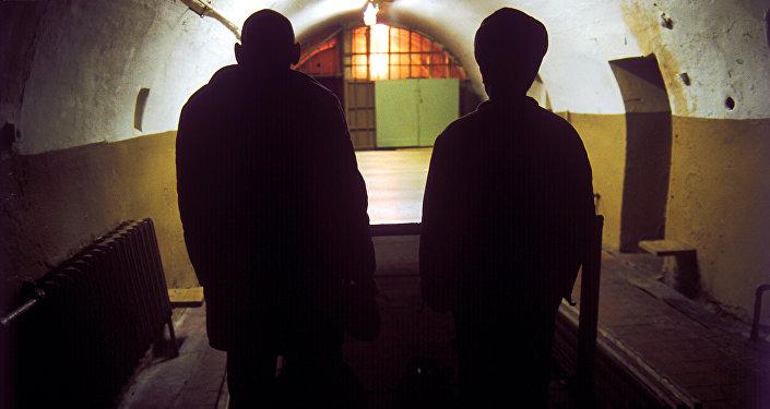 заключенный и надзирательв тюрьме. Архивное фото