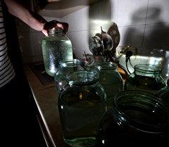 Мужчина набирает воду в банки. Архивное фото