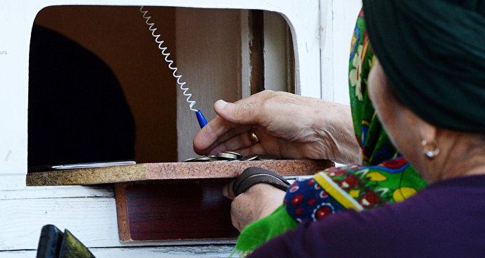 Архивное фото пенсионерки, которая получает пенсию в почтовом отделении
