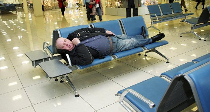 Мужчина спит в зале ожидания аэропорта. Архивное фото