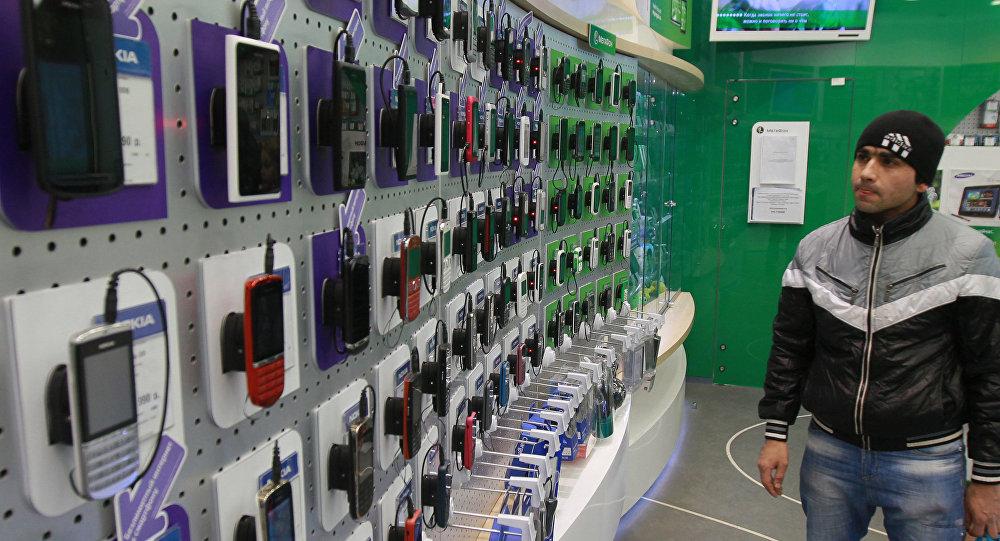 Посетитель у витрины с сотовыми телефонами. Архивное фото