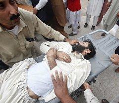 Жер титирөөдөн жабыркаган адам, Пакистан.