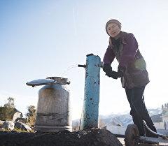 Женщина качает питьевую воду с колонки. Архивное фото