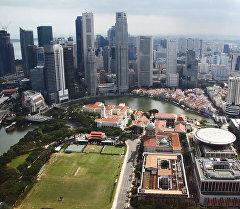 Вид на башни Сити за рекой (Singapore river) и здания старого и нового парламента (на первом плане) в Сингапуре. Архивное фото