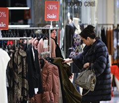 Женщина выбирает одежду во время в магазине. Архивное фото