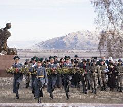 Улуттук гвардиянын жоокерлери венок көтөрүп баратышат.