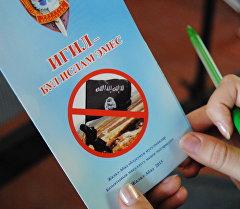 Девушка держит листовку про террористическую группу ИГИЛ.