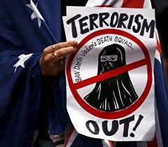 Один из участников митинга в Австралии держит плакат.