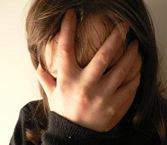 Девушка закрывшая лицо рукой. Архивное фото