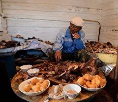 Мясник готовит мясо к столу. Архивное фото