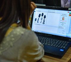 Оператор проверяет биометрические данные гражданина Кыргызстана. Архивное фото