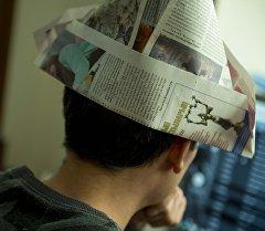 Газетадан жасалган шляпа кийген бала. Архив