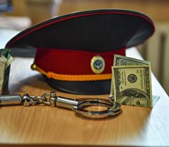 Милиция кызматкеринин фуражкасы, акча жана кол кишен. Архив