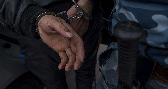 Задержанный мужчина в наручнике. Архивное фото