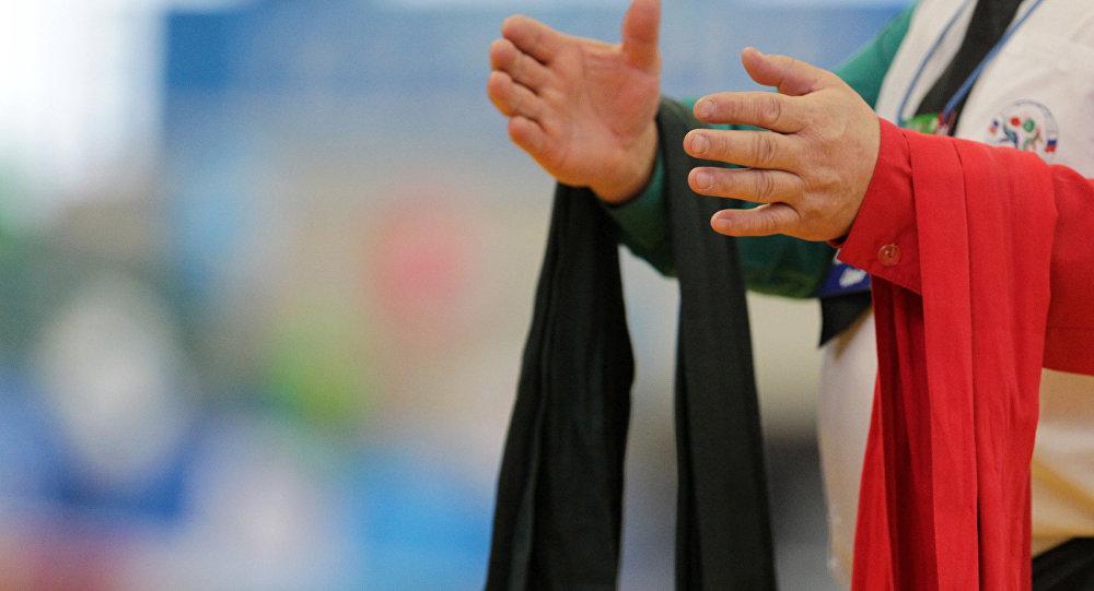 Пояса разного цвета на руках судьи перед поединком на чемпионате по борьбе на поясах. Архивное фото