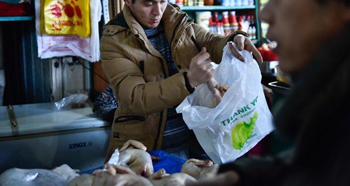 Продавец на рынке кладет окорочку в пакет. Архивное фото