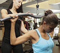 Девушка во время занятия с тренером в тренажерном зале.  Архивное фото