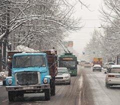 Автомобили на улице во время снегопада. Архивное фото