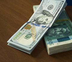 Пачка сто долларовых и пяти тысячи сомовых купюр на столе. Архивное фото